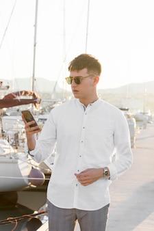 Vorderansicht des mannes am yachthafen mit smartphone und sonnenbrille
