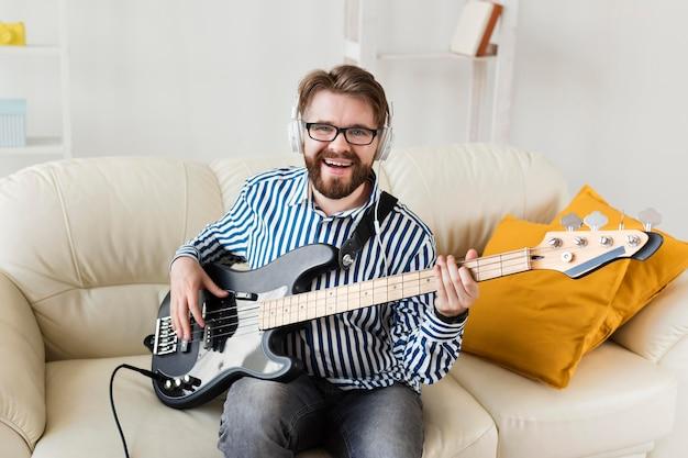 Vorderansicht des mannes auf sofa mit e-gitarre