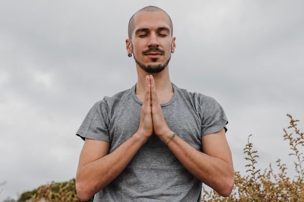 Vorderansicht des mannes außerhalb, der yoga tut