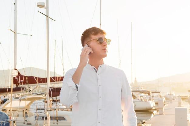 Vorderansicht des mannes, der am telefon draußen am yachthafen spricht