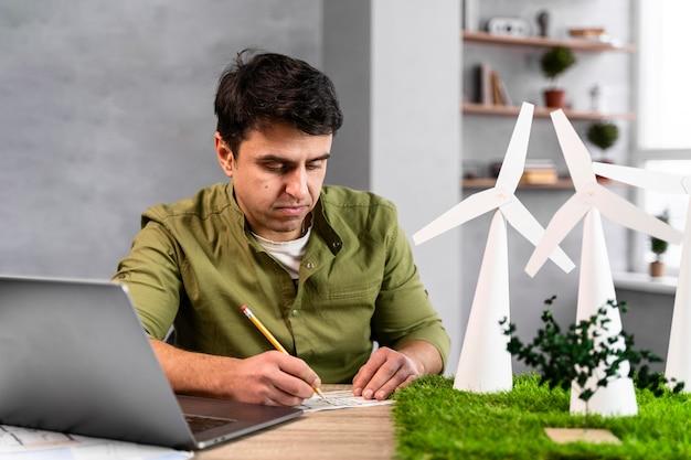 Vorderansicht des mannes, der an einem umweltfreundlichen windkraftprojekt arbeitet