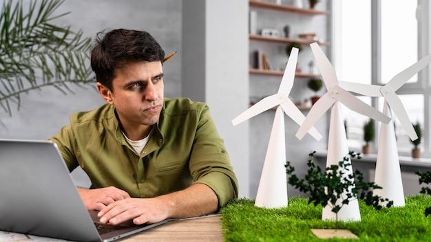 Vorderansicht des mannes, der an einem umweltfreundlichen windkraftprojekt mit laptop arbeitet