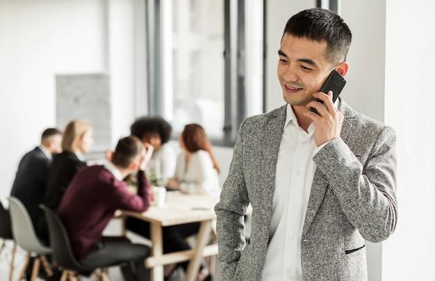 Vorderansicht des mannes, der an seinem telefon spricht
