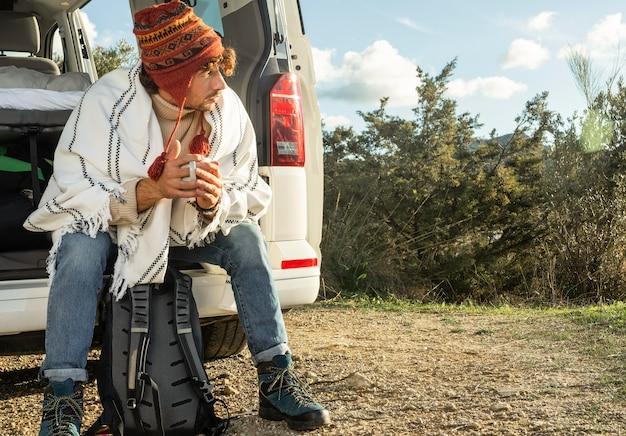 Vorderansicht des mannes, der auf dem kofferraum des autos während einer straßenfahrt sitzt