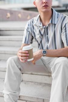 Vorderansicht des mannes, der auf stufen draußen beim halten der tasse kaffee sitzt