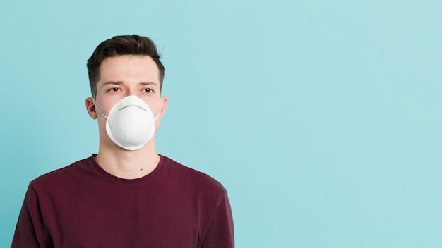 Vorderansicht des mannes, der beim tragen einer medizinischen maske aufwirft, um coronavirus zu verhindern