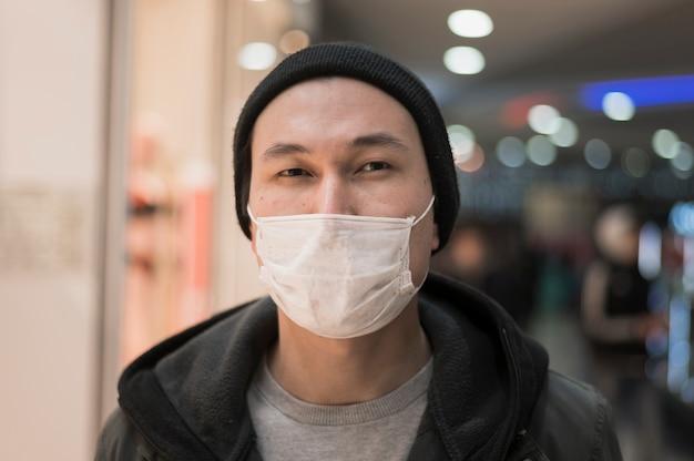 Vorderansicht des mannes, der beim tragen einer medizinischen maske aufwirft