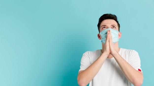 Vorderansicht des mannes, der betet, während er eine medizinische maske trägt