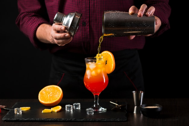 Vorderansicht des mannes, der cocktail in glas gießt