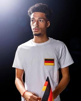 Vorderansicht des mannes, der die deutsche flagge hält