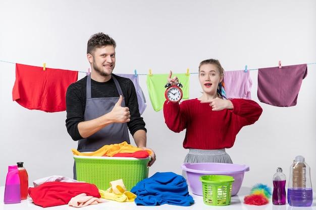 Vorderansicht des mannes, der ein daumen-hoch-zeichen macht und seine frau auf den wecker zeigt, der hinter den wäschekörben des tisches steht und sachen auf dem tisch wäscht