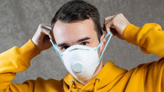 Vorderansicht des mannes, der eine medizinische maske auf gesicht zum schutz trägt