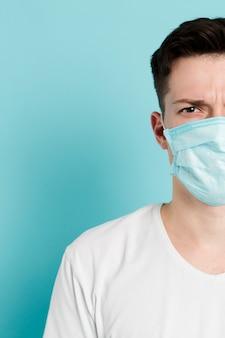 Vorderansicht des mannes, der eine medizinische maske trägt und aufwirft