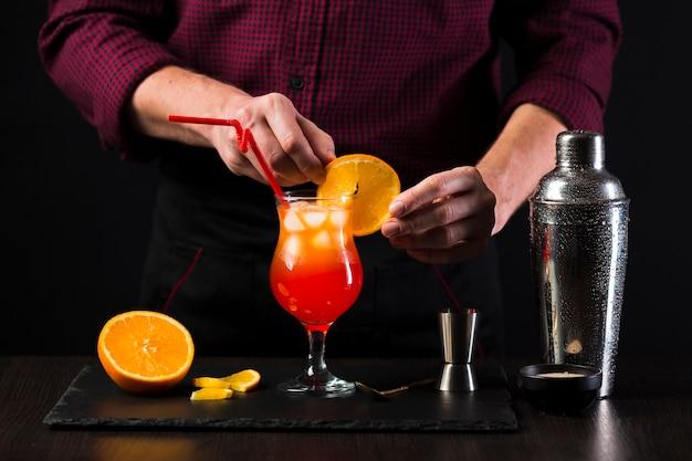 Vorderansicht des mannes, der einen cocktail macht