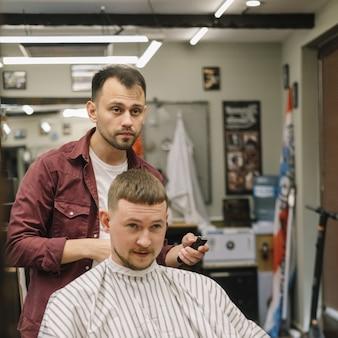 Vorderansicht des mannes, der einen haarschnitt bekommt