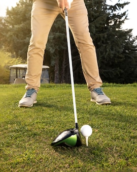 Vorderansicht des mannes, der golf auf dem feld übt