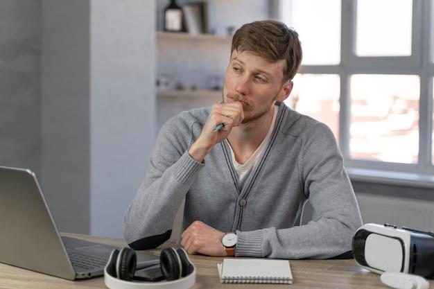 Vorderansicht des mannes, der im medienfeld mit laptop und kopfhörern arbeitet