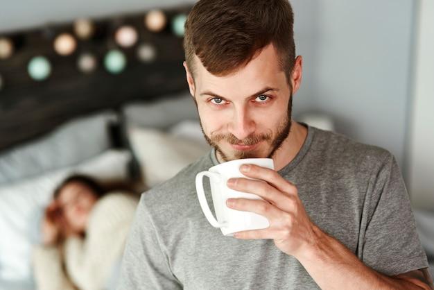 Vorderansicht des mannes, der kaffee im schlafzimmer trinkt