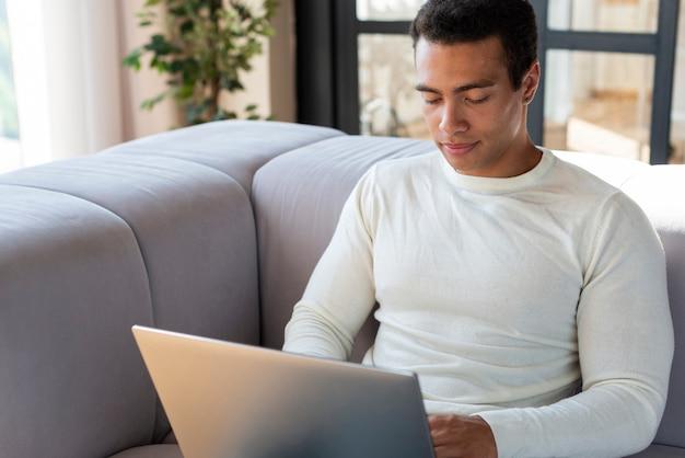 Vorderansicht des mannes, der laptop verwendet