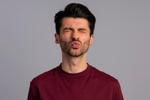 Vorderansicht des mannes, der lippen für einen kuss schmollt