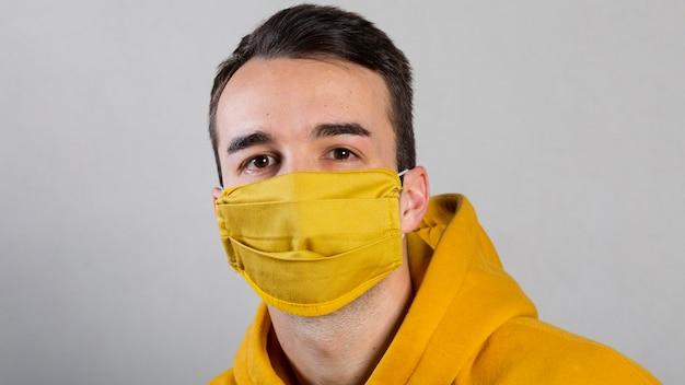Vorderansicht des mannes, der medizinische maske auf gesicht trägt