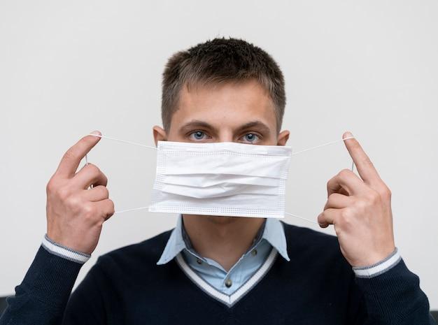Vorderansicht des mannes, der medizinische maske aufsetzt