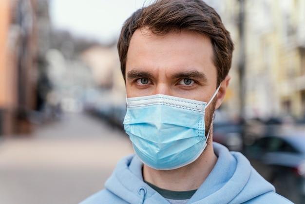 Vorderansicht des mannes, der medizinische maske in der stadt trägt