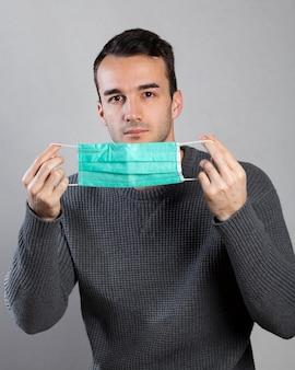 Vorderansicht des mannes, der medizinische maske mit händen hält