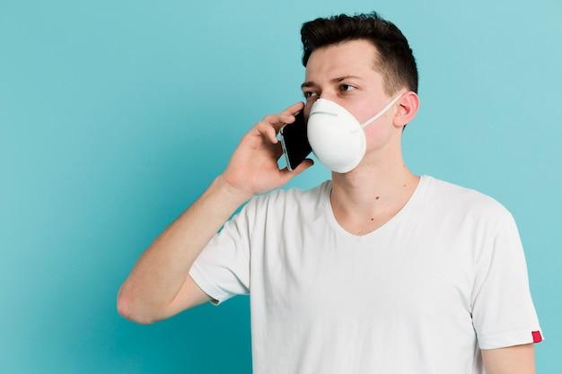 Vorderansicht des mannes, der medizinische maske trägt und auf smartphone spricht