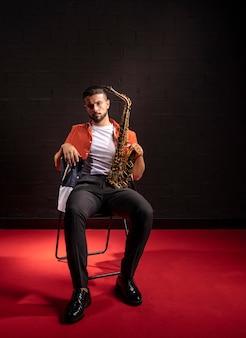 Vorderansicht des mannes, der mit saxophon aufwirft