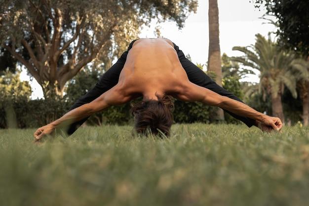 Vorderansicht des mannes, der yoga auf dem gras tut