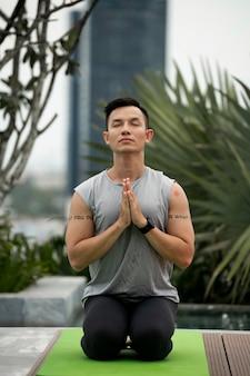 Vorderansicht des mannes, der yoga praktiziert