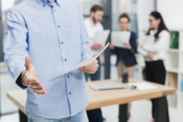 Vorderansicht des mannes im büro, der einen handschlag anbietet