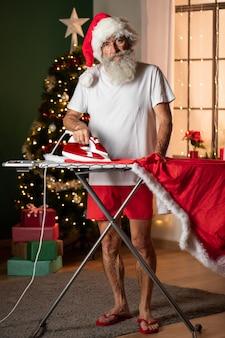 Vorderansicht des mannes im weihnachtsmannhut, der sein kostüm bügelt