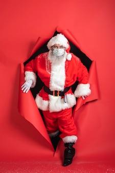 Vorderansicht des mannes im weihnachtsmannkostüm, das aus papier kommt