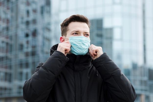 Vorderansicht des mannes in der stadt, die medizinische maske trägt