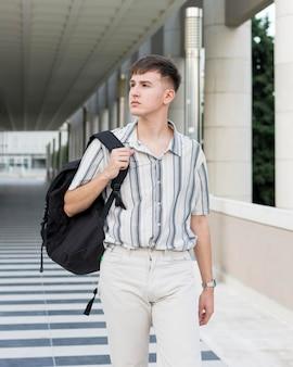 Vorderansicht des mannes in der stadt mit rucksack