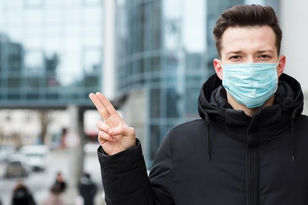Vorderansicht des mannes mit coronavirus, der medizinische maske in der stadt trägt