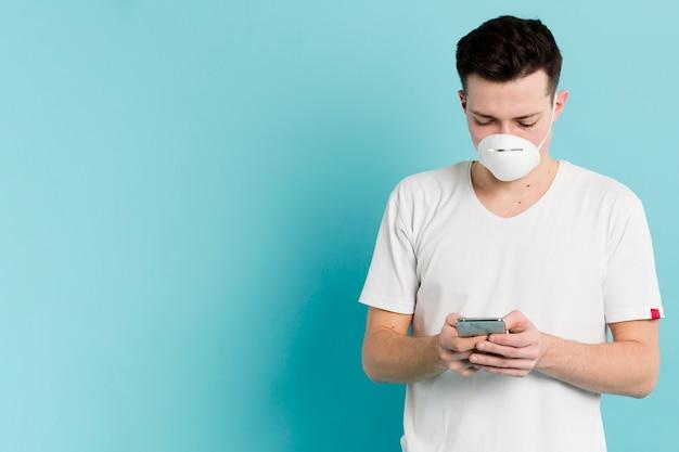 Vorderansicht des mannes mit der medizinischen maske, die coronavirus auf smartphone nachschaut