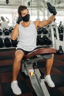 Vorderansicht des mannes mit der medizinischen maske, die ein selfie an der turnhalle nimmt