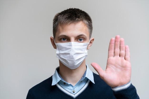 Vorderansicht des mannes mit der medizinischen maske, die palme oben hält