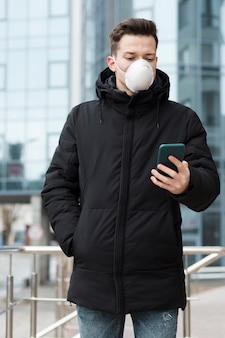 Vorderansicht des mannes mit der medizinischen maske, die sein telefon in der stadt betrachtet