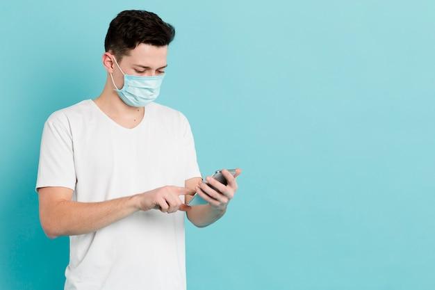 Vorderansicht des mannes mit der medizinischen maske, die smartphone betrachtet