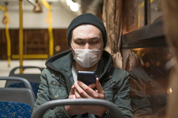 Vorderansicht des mannes mit der medizinischen maske im bus, der sein telefon betrachtet