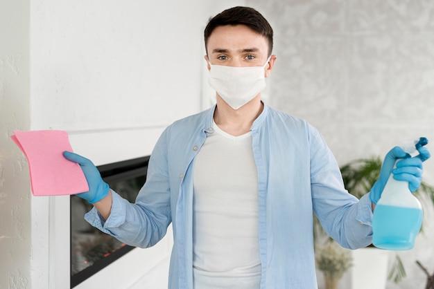 Vorderansicht des mannes mit gesichtsmaske, die reinigungsflüssigkeit hält