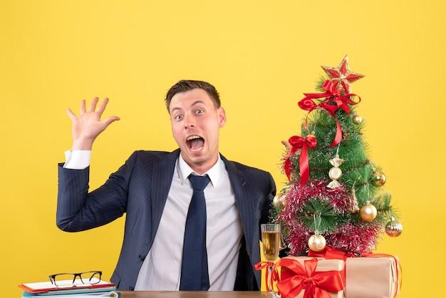 Vorderansicht des mannes mit großen augen, der am tisch sitzt und in der nähe von weihnachtsbaum und geschenken auf gelb hallo sagt
