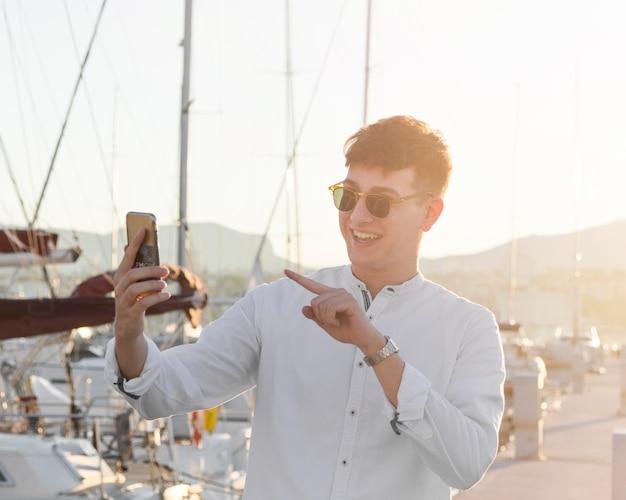 Vorderansicht des mannes mit sonnenbrille, die einen videoanruf am yachthafen hat