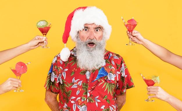 Vorderansicht des mannes mit tropischem hemd und weihnachtsmütze