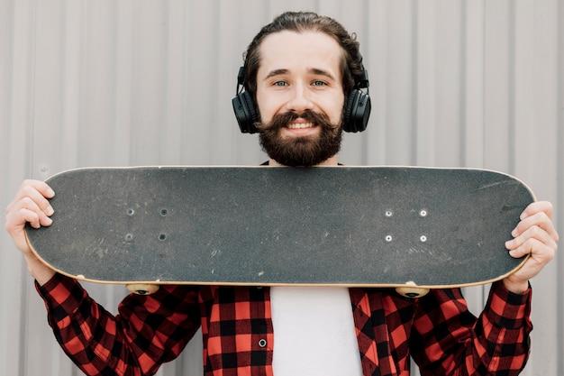 Vorderansicht des mannes skateboard halten