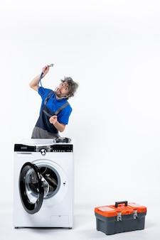 Vorderansicht des mechanikers, der das stethoskop anhebt, das hinter der waschmaschine an der weißen wand steht